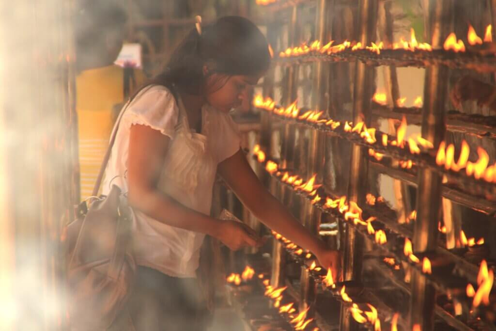 Image of Devotee lights up flames as a religious ritual at Kelaniya