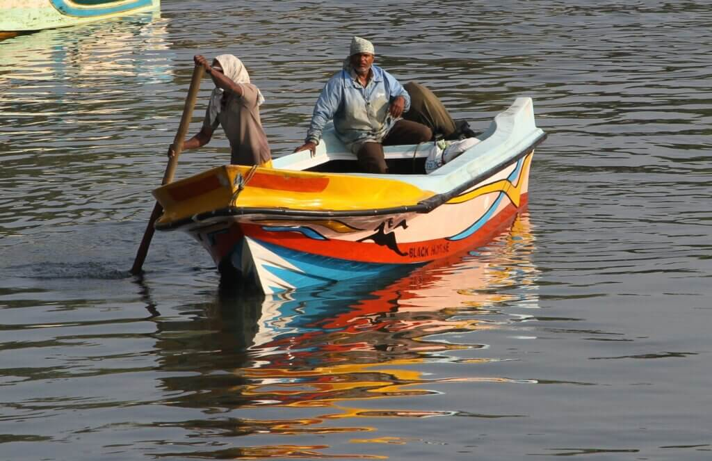 Image of ishermen paddling a boat in the lagoon