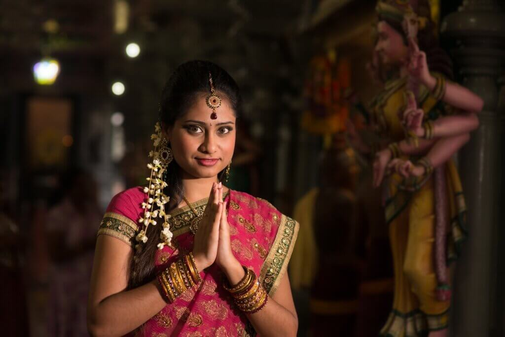Image of Indian girl in traditional sari dress praying in a hindu temple.