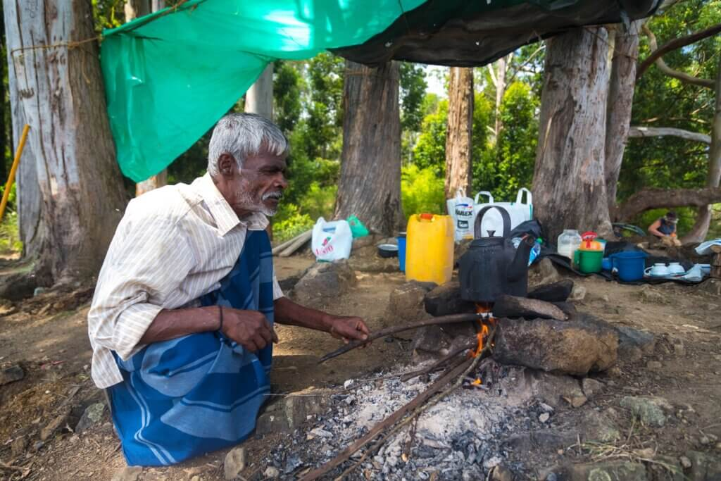 Image of Man boiling water in a pot on camp fire in forest