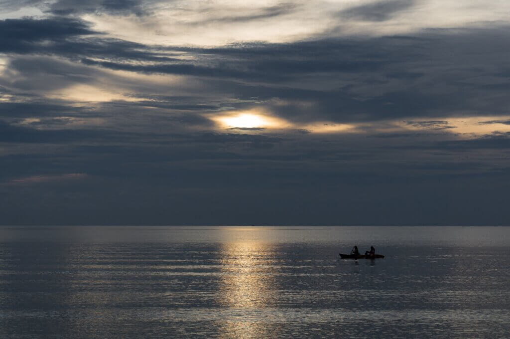 Image of People is taking a kayak while the sun is setting the beach and the sea
