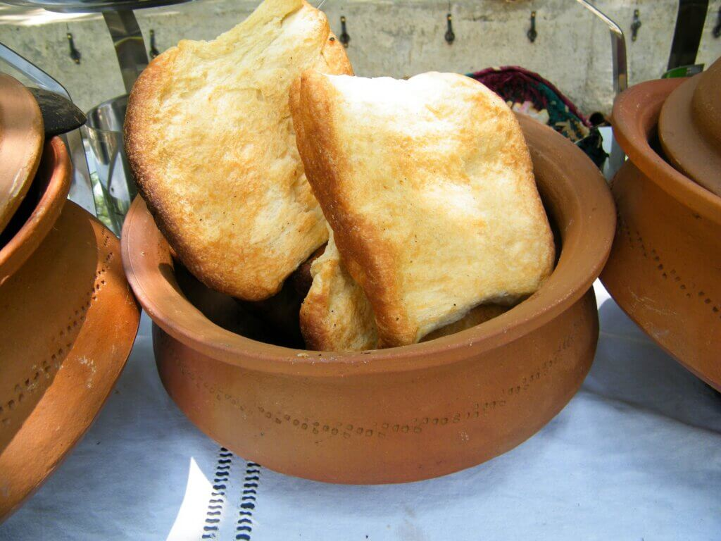 Image of Roasted bread and currys served in earthenware pottery