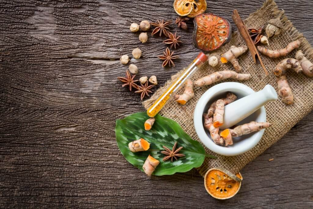 Image of Turmeric in Mortar Grinder drugs and ingredient herbs on wooden background