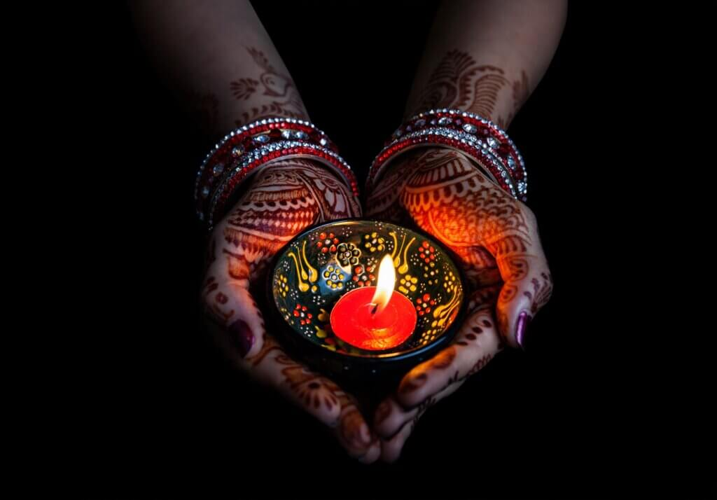 Image of Woman hands with henna holding lit candle