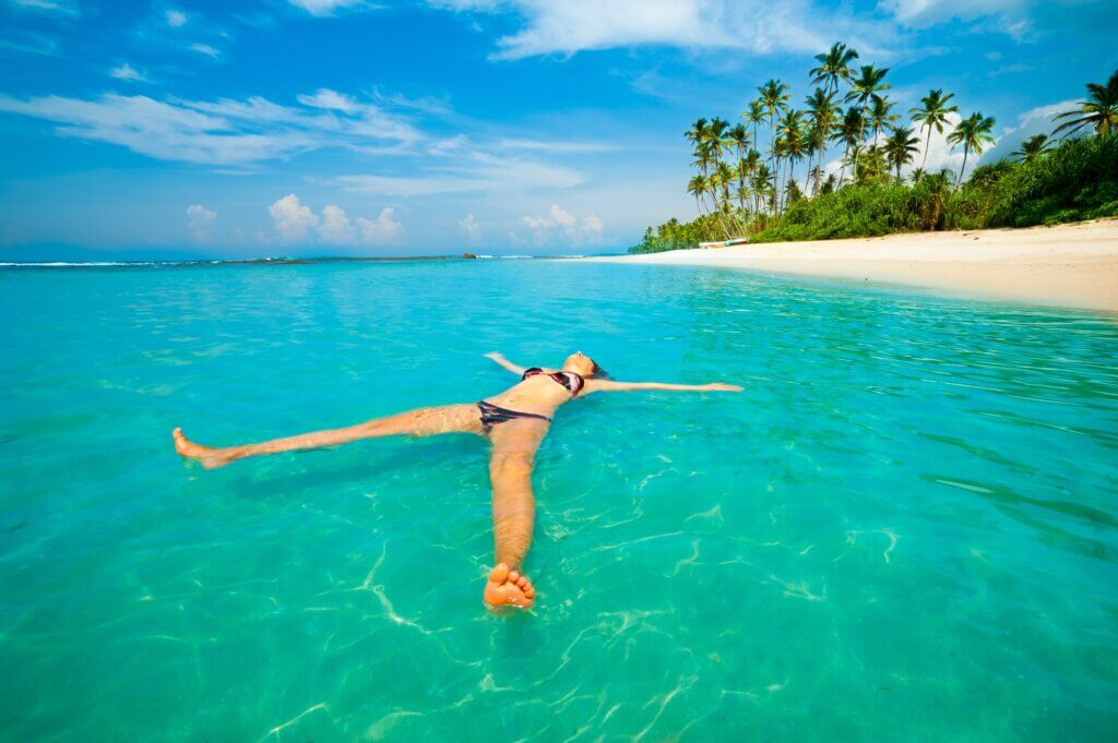 Image of Young woman relax like a sea star in the ocean on a tropical coast
