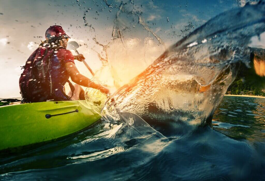 Image of Young lady paddling hard the kayak with lots of splashes