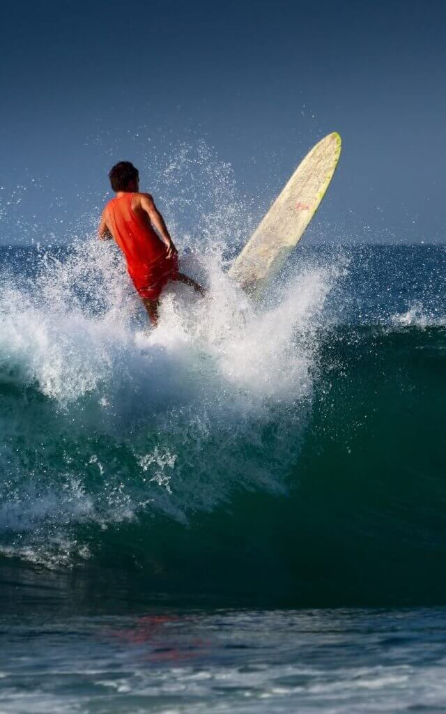 Image of Surfer riding on the wave with long board Midigama beach