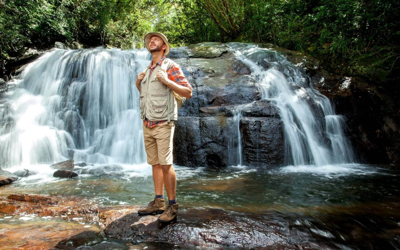 Image of Hiker standing in front of a waterfall deep in the jungle