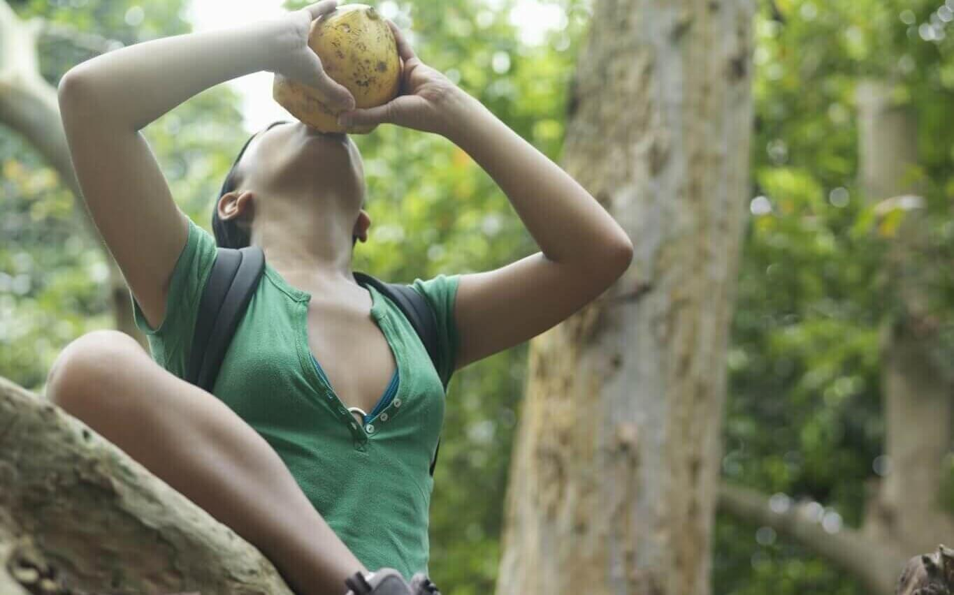 Image of view of a young woman in tropical forest drinking from coconut